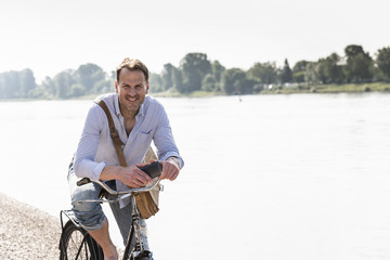 Mature man with bike and smartphone at Rhine riverbank