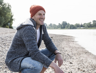 Smiling mature man with red beanie at Rhine riverbank