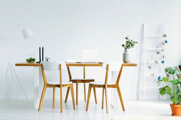 Bright and natural start-up office interior with a laptop and three wooden chairs around a simple desk. Real photo