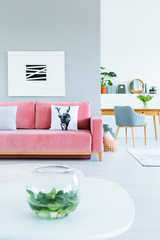 Apartment interior for a freelancer with a gray armchair and wooden desk in the background and a painting above pink sofa in the living room. Real photo