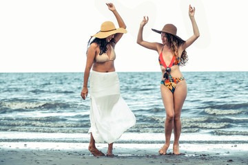 Happy women dance on sand beach in summer.