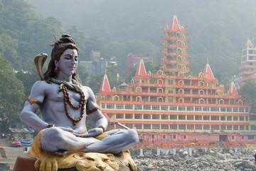 Statue of Shiva sitting in meditation on the riverbank of Ganga in Rishikesh, Tera Manzil Temple, Trayambakeshwar in background Wall mural