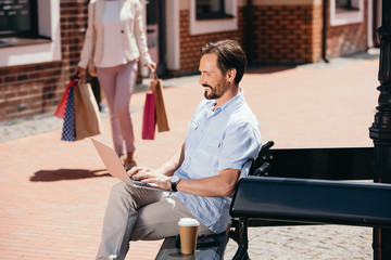 handsome man sitting on bench with laptop, woman walking with shopping bags on street