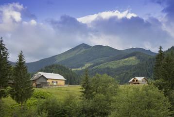 Photo of mountain village in the summer under beautiful cloudy sky. Ukraine, Carpathians, Dzembronia