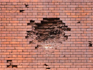 Echoes of war. Wall damaged by a military projectile (bomb), broken red brickwork. Brest fortress,...