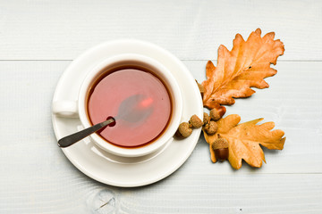Mug filled with black brewed tea, spoon and autumn fallen leaves on white background. Autumn drink concept. Tea served with spoon, sugar and decor acorn and leaves. Drink and acorn and oak leaves