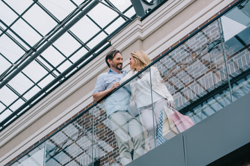 low angle view of couple standing on balcony in shopping mall