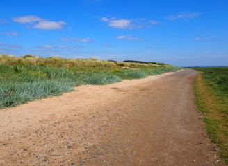single land dirt road mad of sand and stones extending to the distance with grass covered dunes and bright blue summer sky near the ribble estuary in lancashire england