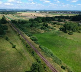 Electric railroad in a green natural environment, meadows, trees, grass, aerial view