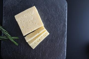 cheese cut on a stone dark background