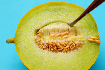 A juicy honeydew melon and a spoon