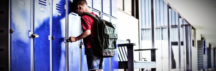 Full length of boy leaning on lockers in corridor