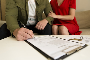 Young happy couple signing real estate purchase contract.