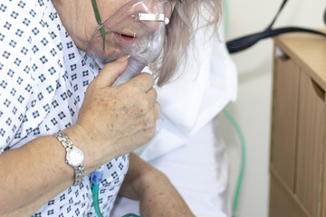 Woman in hospital with breathing difficulties using a resperation mask