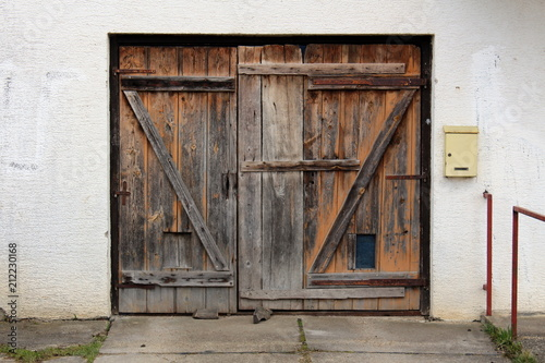 Old Dilapidated Wooden Garage Doors With Rusted Metal Hinges And Small Mailbox Mounted On Right Side