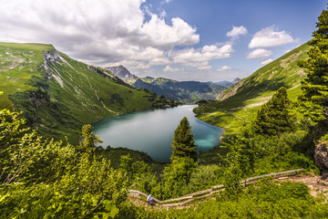 Man with backpack hiking in Tannheim Valley with the picturesque mountain lake Traualpsee in the background surrounded by green meadows and forest, Tyrol, Austria