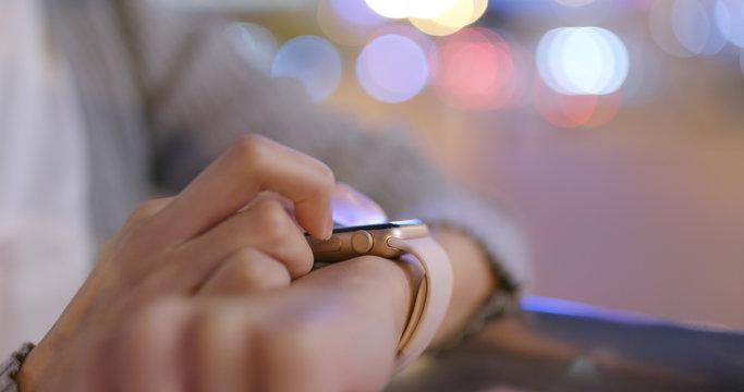 Business woman using smart watch at night
