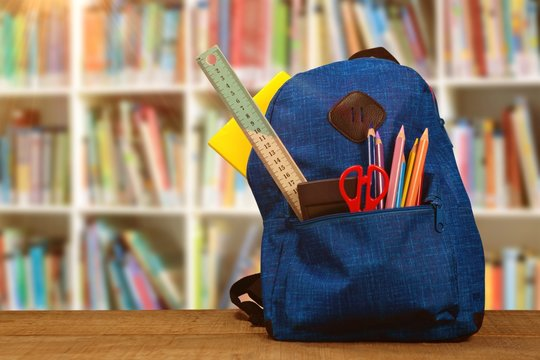 Composite image of bag with school supplies on wooden table