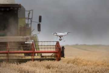 Drone flying in front of combine harvester