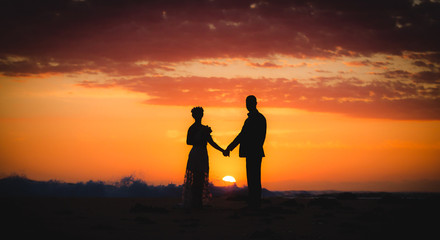 silhouette of couple lovers, bride and groom holding hands during sunrise time at the beach with beautiful pink sunrise sky.