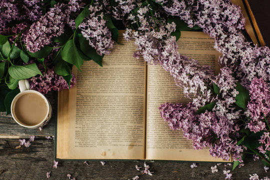 Cup of tea, lilac flowers, book on dark wooden background