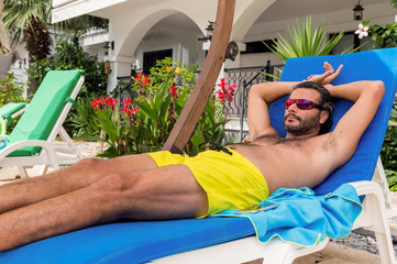 Bearded Caucasian man with sunglasses resting on a sunbed in a resort