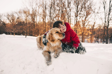 Portrait of a boy sitting in the snow with his golden retriever dog