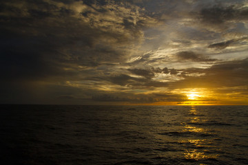 Beautiful sunset on the ocean with a dramatic cloud and golden sunset sky