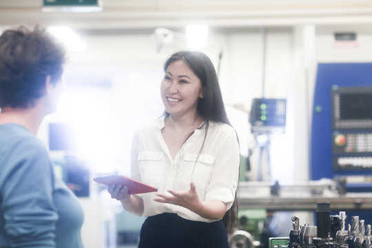 Smiling female engineer standing in a workshop talking to a colleague