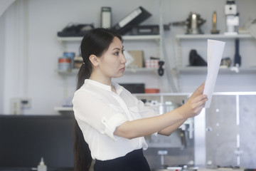 Female engineer standing in a workshop looking at technical drawings