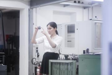 Female engineer examining a drill bit