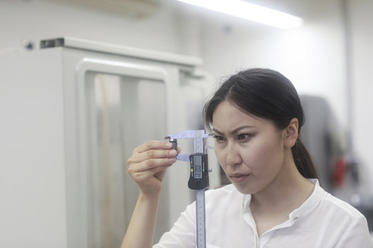 Female engineer using a measuring stick