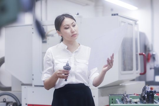 Female engineer looking at a technical drawing and examining a drill bit