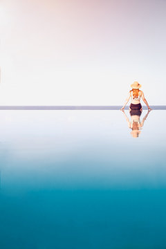 Woman sitting on the edge of an infinity pool