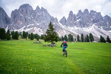 Woman mountain biking near Funes, Trentino, South Tyrol, Italy