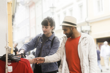 Couple standing in street clothes shopping