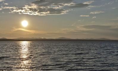 dark grey evening sky over the lake, orange sun