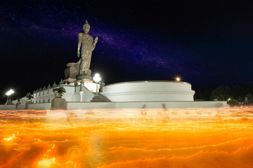 Beautiful milky way and big buddha statue at night and moving candle light in Makha Bucha day.