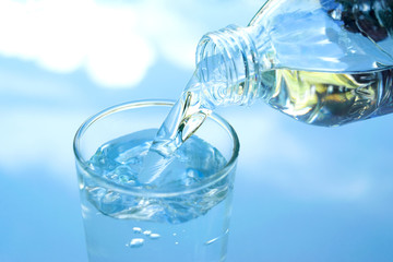water in glass put on table under the blue sky reflection for healthy or drink, nature concept.