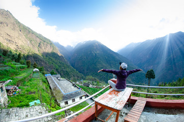 Woman meditating doing yoga outside of their house, the way to Annapurna base camp, Nepal. travel concept and nature