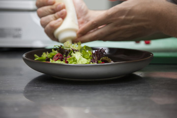 The cook prepares a salad with cherries