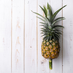 Pineapple on white wooden background