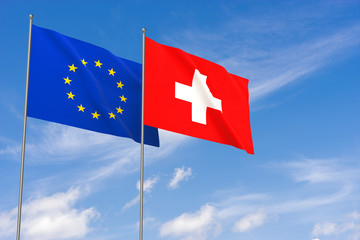 European Union and Switzerland flags over blue sky background.