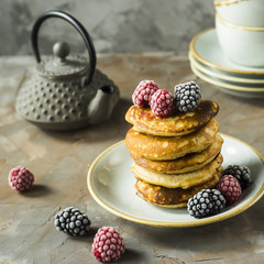 A pile of pancakes on a plate with raspberries and blackberries next to cups and a kettle on a gray table. Summer Breakfast concept