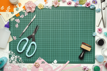 The cutting mat is surrounded by paper flowers, paper, tools and scrapbooking materials. Scrapbooking, top view