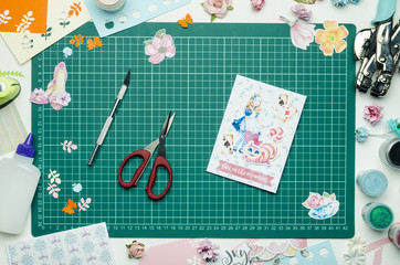 Homemade greeting card and tools on the cutting Mat. Scrapbooking, top view
