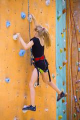 little girl climbing up the wall