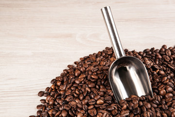 Wall Mural - roasted coffee beans with scoop on a wooden background