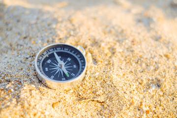 Travel compass on sand.