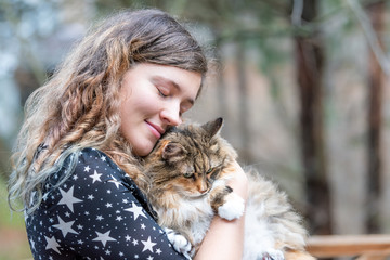 Happy young woman in dress holding maine coon cat outside, outdoors during summer in park with eyes closed